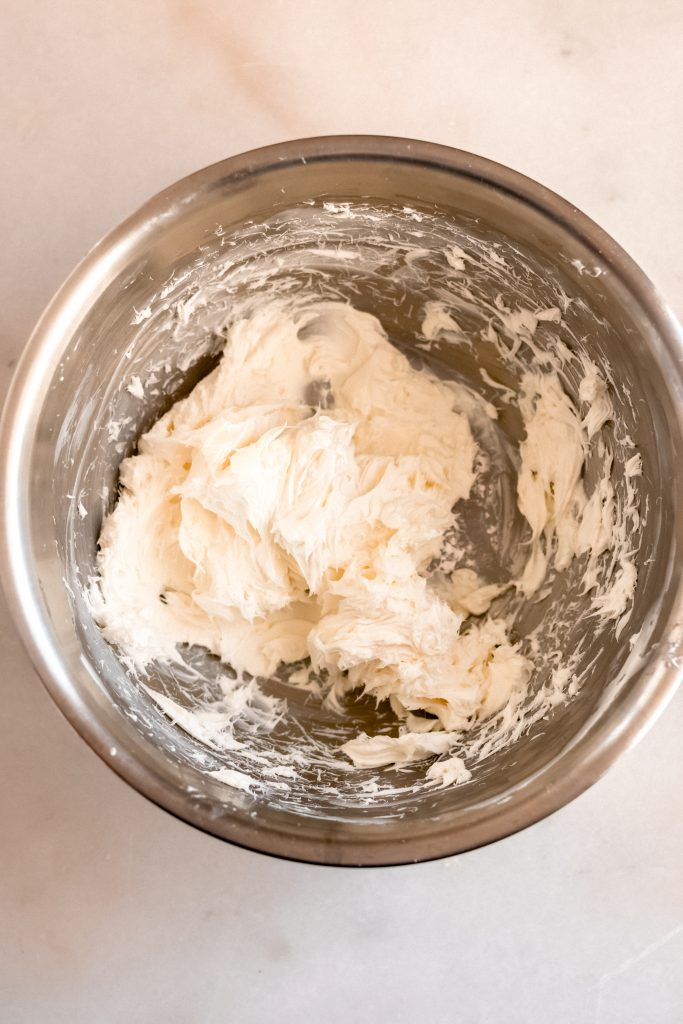 cream cheese whisked in a mixing bowl until creamy
