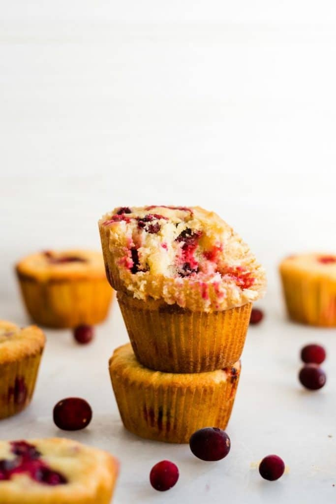 3 cranberry orange muffins stacked on top of one another with muffin liner pulled away from top muffin