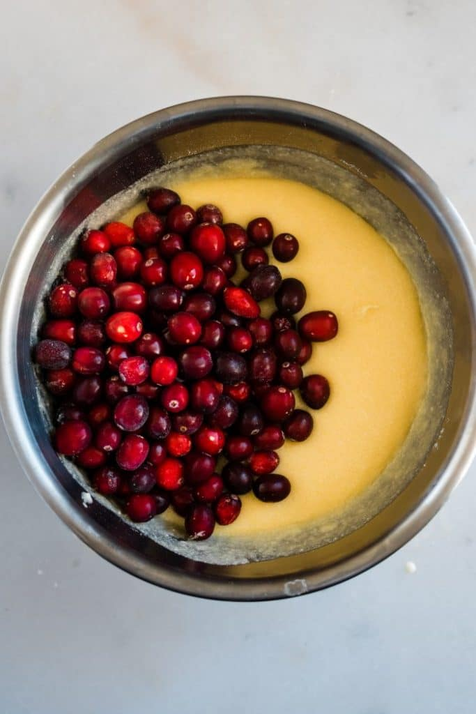 large stainless steel mixing bowl with muffin batter and fresh cranberries