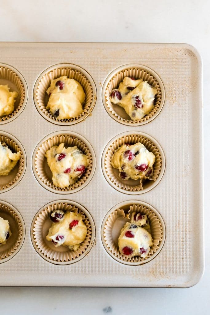 keto cranberry orange muffin batter scooped into individual muffin liners in a muffin tin atop a white countertop