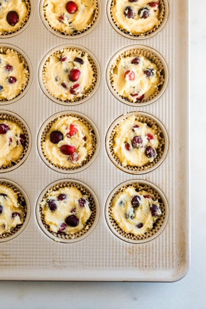 keto cranberry orange muffin batter scooped into individual muffin liners spread evenly and ready to be baked