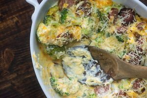 Oval dish of broccoli & smoked sausage casserole with a wooden spoon