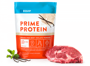a pack of equip vanilla protein powder beside a slab of raw meat and vanilla pods