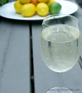 wine glass with white wine spritzer and citrus fruits in the background