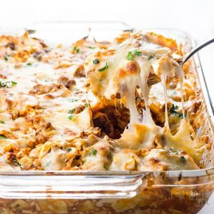 Cabbage roll casserole being scooped out of glass dish