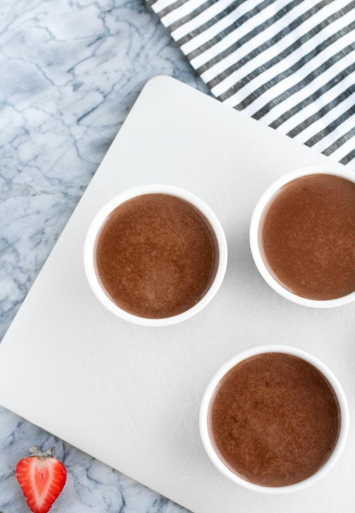 chocolate strawberry panna cotta mixture in three ramekins