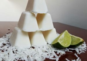 Coconut Fat Bombs stacked into a pyramid beside lime wedges and desiccated coconut