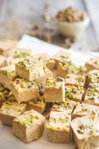 Almond Pistachio Fat Bombs spread and stacked on parchment paper