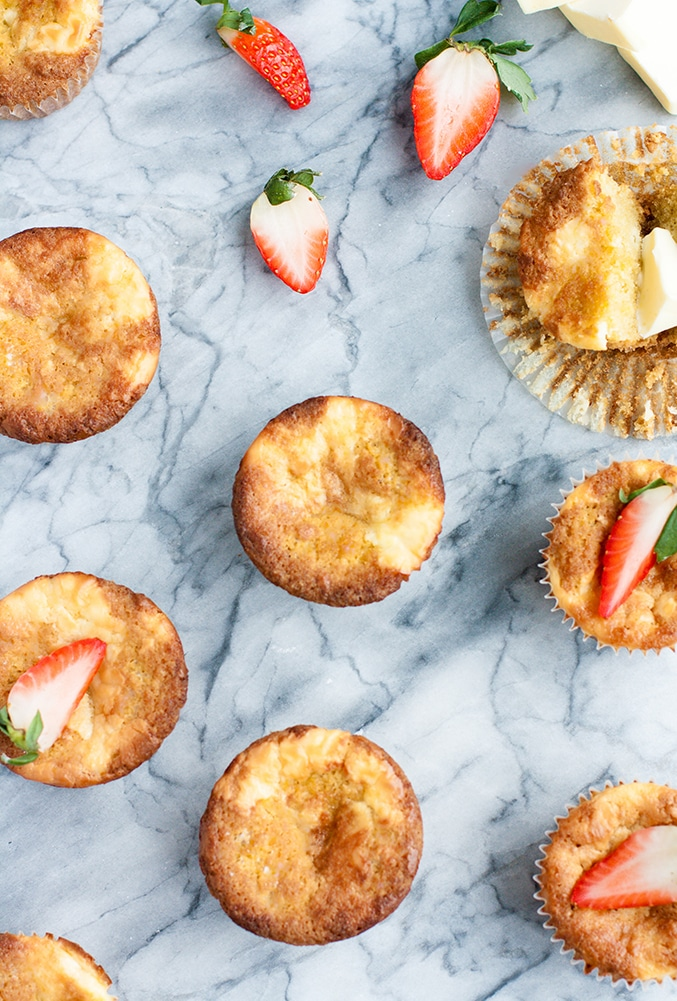 Strawberry Cream Cheese Muffins atop a marble kitchen counter surrounded by halved strawberries