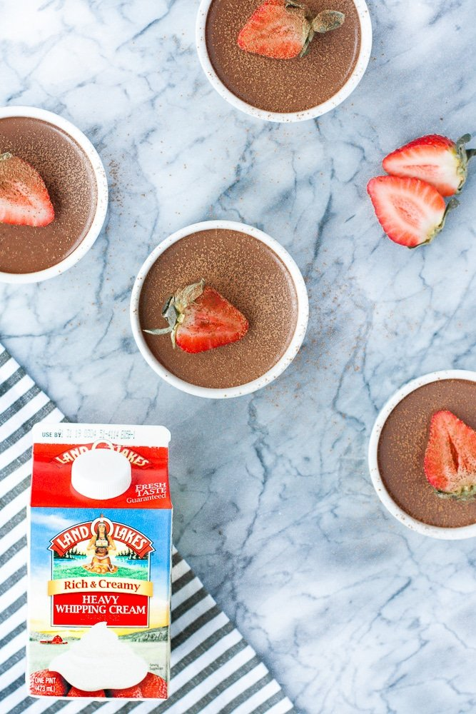 four servings of chocolate strawberry panna cotta atop a marble kitchen counter beside a carton of land o lakes heavy whipping cream