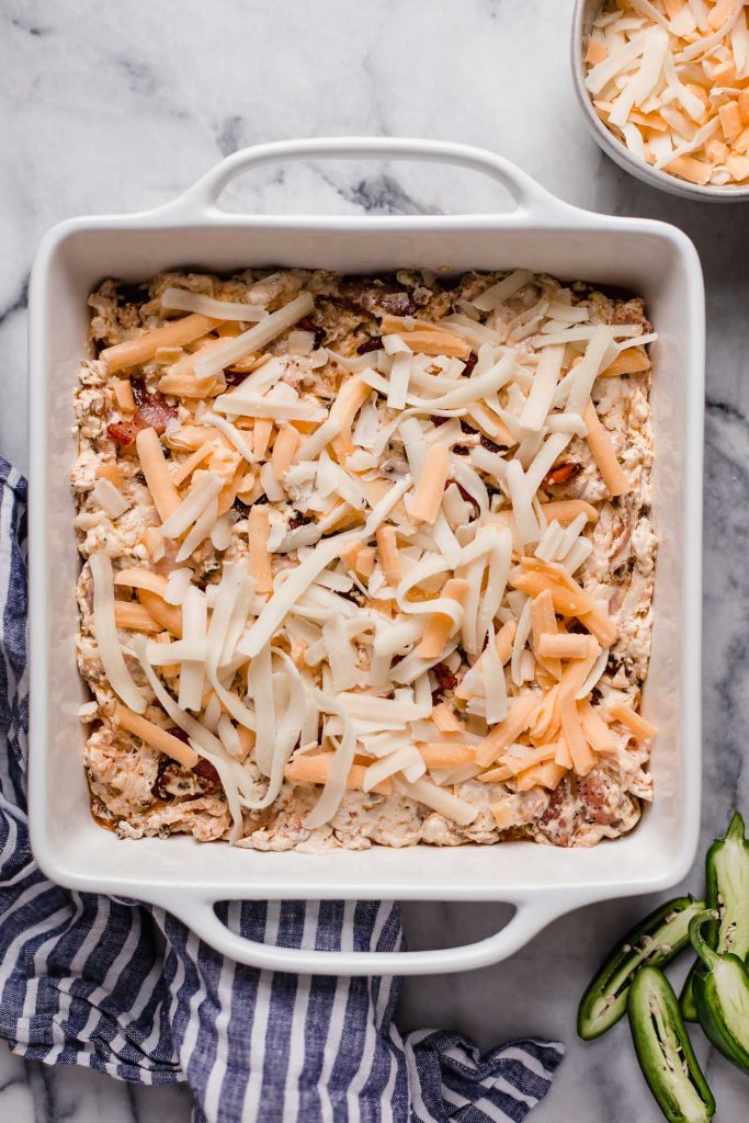 baking dish with shredded chicken and cream cheese mixture with mozzarella and cheddar cheese