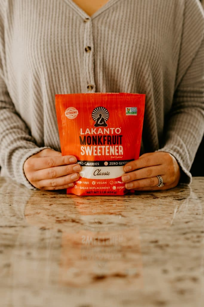 sara nelson of real balanced wearing a gray shirt posing with bag of Lakanto monk fruit sweetener atop marble countertop