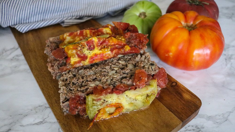 The Best Keto MEatloaf on a cheeseboard beside fresh whole tomatoes