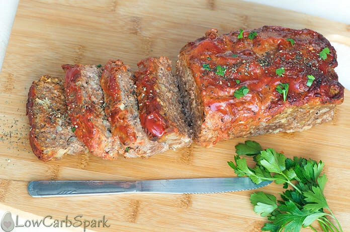 Easy Keto Meatloaf on a chopping board with parsley and a knife