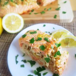 Easy Crab Stuffed Salmon with Lemon Butter on a small plate with lemon wedges