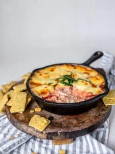 keto chicken parmesan dip in a skillet atop a wooden plate with crackers
