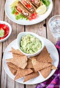 low carb flaxseed paleo tortilla chips on a plate with dip and tacos in the background
