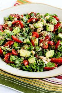 tomato salad with avocado, tuna, cilantro, and lime on a plate atop a striped table napkin