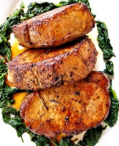 3 rosemary garlic butter pork chops surrounded by cooked spinach