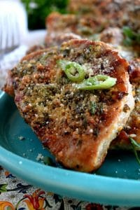 parmesan pork chops on a teal plate with chives on top