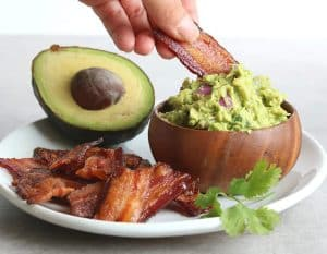 bacon chips and thick guacamole dip on a plate beside a halved avocado and a sprig of parsley
