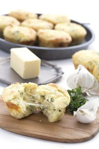 cheesy garlic bread muffins in a baking pan beside a stick of butter