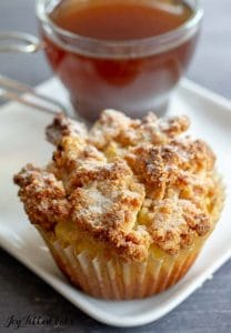Coffee Cake Muffins on a square plate beside a cup of tea