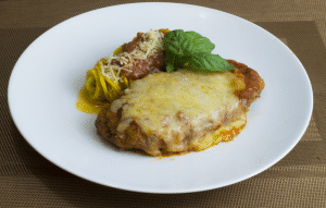 easy keto chicken parmesan bake with spiralized yellow squash on a white plate