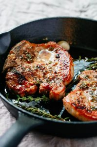 garlic butter baked pork chops in a cast iron skillet
