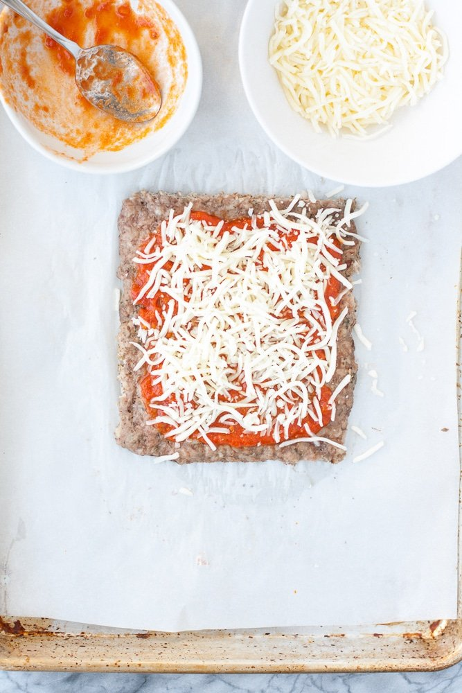 baked ground pork mixture slathered with tomato sauce and sprinkled with cheese on a sheet of parchment paper beside bowl of cheese and tomato sauce