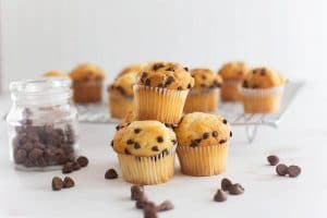 fluffy chocolate chip keto muffins beside a jar of chocolate chips