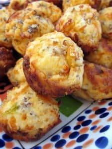 sausage and cheese muffins piled on a plate