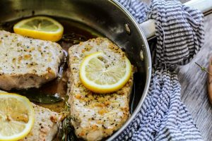 lemon pepper pork chops topped with lemon slices in a metal pan wrapped with striped cloth