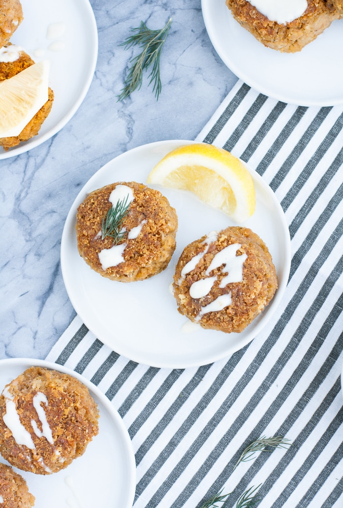 overhead shot of 2-serving low carb tuna cakes on a white plates beside a wedge of lemon