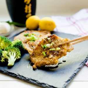 Asian garlic pork chops being picked up with chopsticks on a slate surface