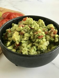 easy fresh homemade guacamole in a black bowl with sliced tomatoes on a chopping board in the background