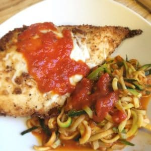 keto breaded chicken parmesan and zoodles on a white dinner plate