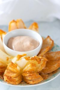 keto blooming onion on a plate with dip in a small ceramic bowl