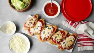 chicken parmesan  on a white plate with ingredients surrounding