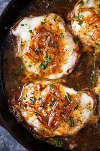 top view of french onion smothered pork chops in a skillet