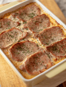cheesy spaghetti squash casserole with pork chops in a white casserole dish atop a wooden cutting board