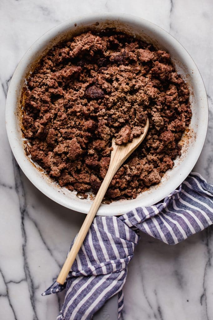 ground beef cooked until browned on a large pan with a wooden mixing spoon