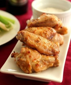 low carb thai curry chicken wings on a rectangular plate with dip and a plate of celery sticks on the background