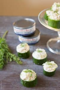 tuna in cucumber cups with 2 cans of tuna in the background