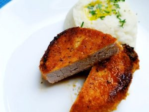 easy shake 'n bake keto pork chops on a white plate with cauliflower mash