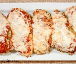5 breasts of baked chicken parmesan layered on a serving plate