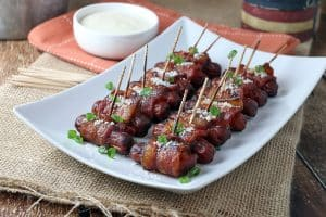 BBQ bacon wrapped smokies on a rectangular ceramic plate with dip