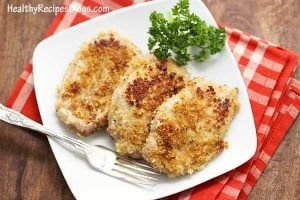 Pork rind crusted pork chops on a square white plate atop a red checkered cloth