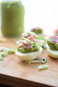 pesto deviled eggs on a wooden board