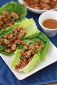 chicken lettuce wraps on a rectangular plate beside dip